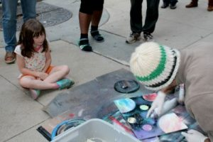 Rose Laube, 7, of Genesee watches intently as Dan Lauber works on creating a stunning spray painted planet paining.
